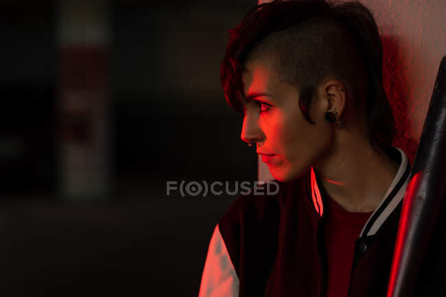 Side view of contemporary female in bomber jacket looking away while leaning on wall with black baseball bat on shoulder with red light on background — Stock Photo