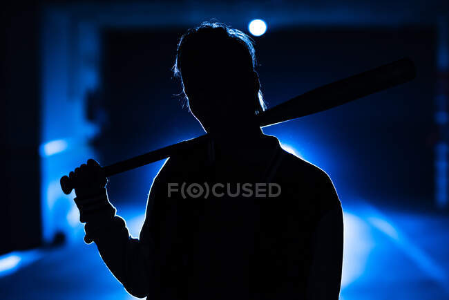 Unrecognizable rebel woman silhouette shadow with modern hairstyle holding bat among colorful blue light and steam — Stock Photo