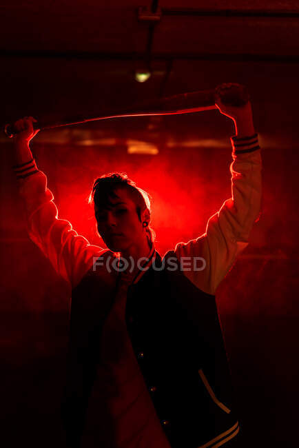Rebel woman in casual jacket with piercing and modern hairstyle holding bat among colorful red light and steam — Stock Photo