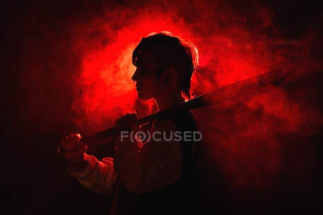 Бунтарка в куртке с пирсингом и современной прической держит летучую мышь среди яркого красного света и пара — стоковое фото
