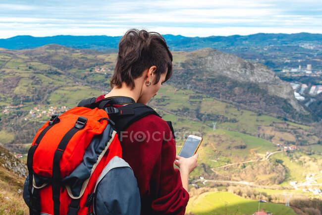 Turista con zaino e smartphone escursioni su strada in collina sotto il cielo nuvoloso in Spagna — Foto stock