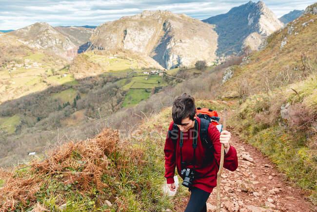 Tourist mit Rucksack und Stock schaut beim Wandern auf Bergstraße unter bewölktem Himmel in Spanien weg — Stockfoto