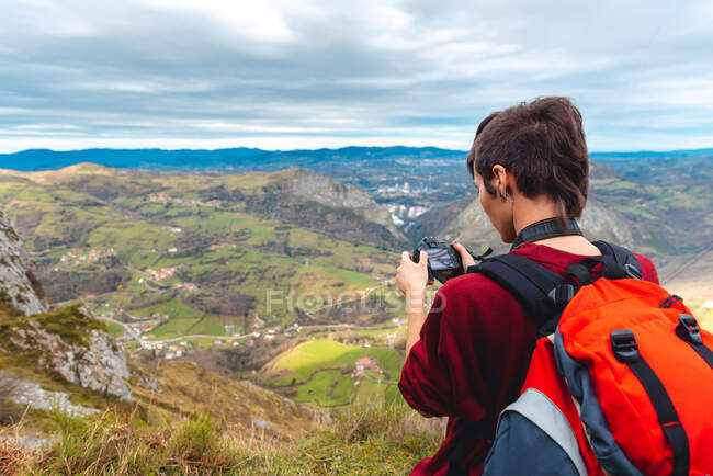Side view of woman with backpack standing on glade and taking shot with camera of magnificent valley against foggy ridges at horizon under sky with fluffy clouds in Spain — Stock Photo