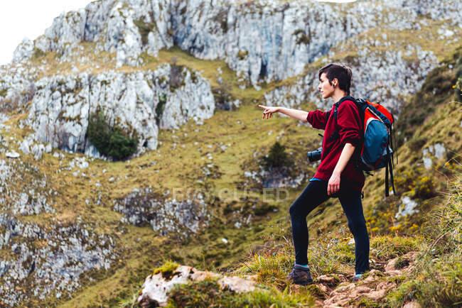 Rückansicht von unkenntlichen Touristen mit rotem Rucksack, die malerische Aussicht auf Bergkämme unter wolkenverhangenem Himmel beim Wandern und Berühren der Kapuze in Monsacro bewundern — Stockfoto
