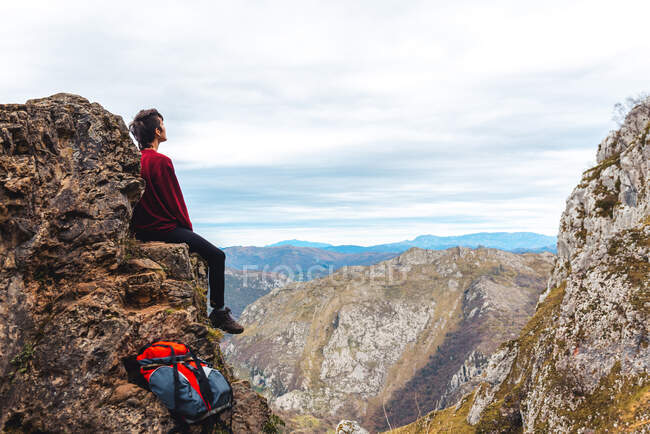 Side view of tourist sitting on edge of cliff enjoying freedom and admiring amazing scenery of countryside located in valley at mountain foothill against foggy forested hills and plain under sky with lush gray clouds in Spain — Stock Photo