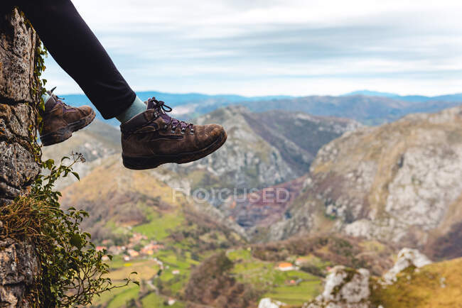 Side view of legs tourist sitting on edge of cliff enjoying freedom and admiring amazing scenery of countryside located in valley at mountain foothill against foggy forested hills and plain under sky with lush gray clouds in Spain — Stock Photo