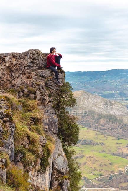 Вид сбоку на туриста, сидящего на краю скалы, наслаждающегося свободой и восхищающегося удивительной живописностью сельской местности, расположенной у подножия горы на фоне туманных холмов и равнины под небом с пышными облаками в Испании — стоковое фото