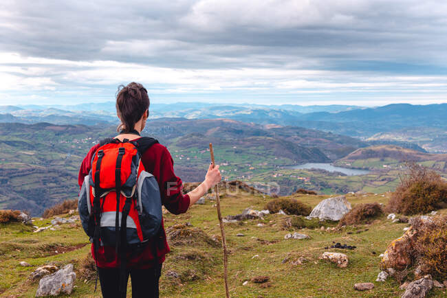 Back view of unrecognizable hiker with backpack and stick standing with arms outstretched and enjoying freedom viewing majestic scenery of countryside located along river shore in valley against foggy ridges at horizon under cloudy sky in Spain — Stock Photo