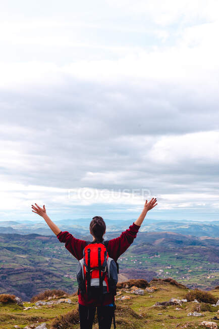 Back view of unrecognizable hiker with backpack standing with arms outstretched and enjoying freedom viewing majestic scenery of countryside located along river shore in valley against foggy ridges at horizon under cloudy sky in Spain — Stock Photo