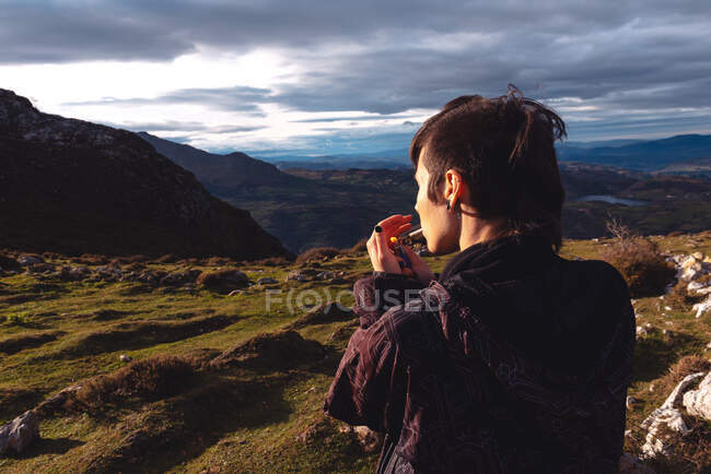 Back view of provocative confident female traveler with trendy hairstyle in casual clothes lighting cigarette while looking away and enjoying wonderful scenery of highland under dramatic clouds in evening in Spain — Stock Photo