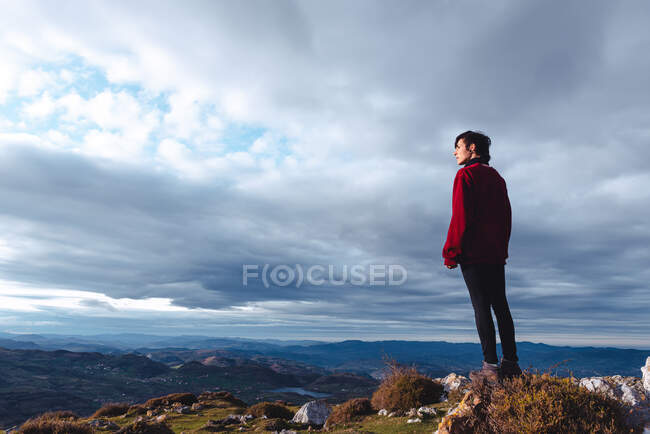 Hiker standing and enjoying freedom viewing majestic scenery of countryside located along river shore in valley against foggy ridges at horizon under cloudy sky in Spain — Stock Photo