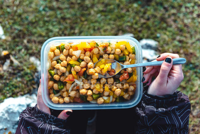 From above crop woman in warm jacket holding plastic container of chickpea with veggies having lunch on meadow while hiking in Spain — Stock Photo