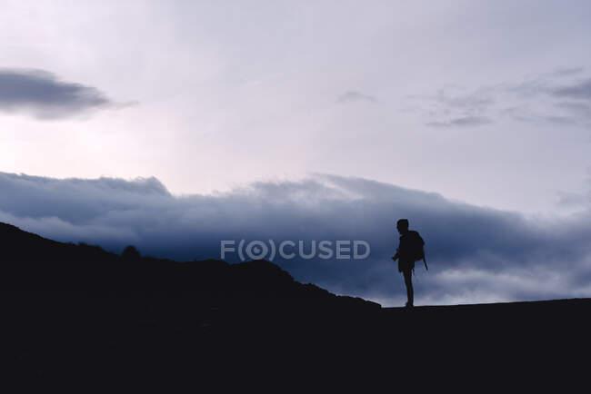 Vista lateral silueta de mujer con mochila de pie sobre el claro con cámara en magnífico valle contra crestas de niebla en el horizonte bajo el cielo con nubes esponjosas en España - foto de stock