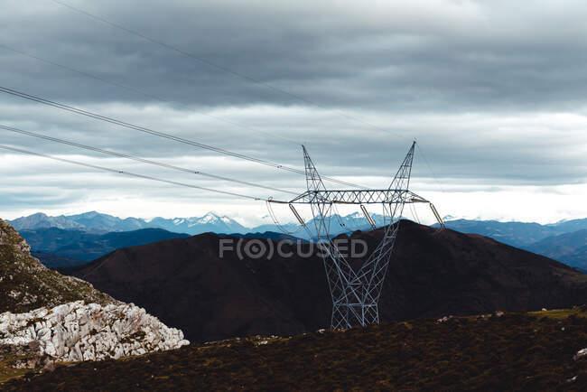 Высокий столб электричества с высоковольтными кабелями в высокогорье против снежных горных хребтов на горизонте под серым облачным небом в Испании — стоковое фото
