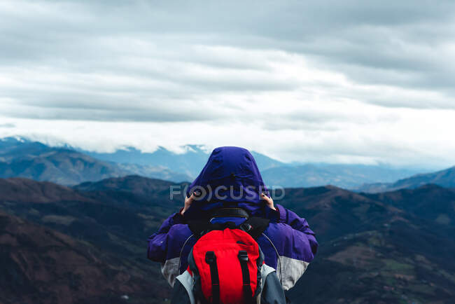 Back view of unrecognizable tourist in violet jacket with red backpack admiring picturesque view of mountain ridges under cloudy sky while standing and touching hood in Monsacro — Stock Photo