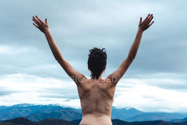 Vue arrière de la femelle libre topless debout avec les bras levés jouissant de la liberté et de la sauvagerie tout en regardant des paysages idylliques de montagne brumeuse par temps couvert en Espagne — Photo de stock