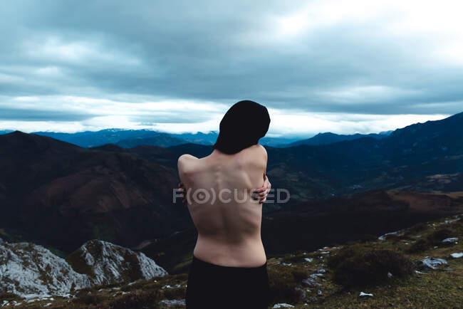 Visão traseira de livre topless feminino de pé desfrutando de liberdade e selvageria enquanto visualiza cenário idílico de montanha nebulosa em tempo nublado na Espanha — Fotografia de Stock