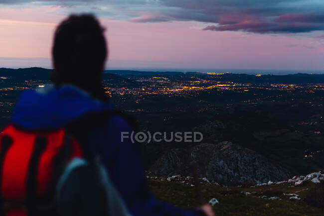 Vue arrière du touriste avec sac à dos et bâton regardant loin et admirant des paysages pittoresques lors de la randonnée sur la route des collines sous un ciel nuageux en Espagne — Photo de stock