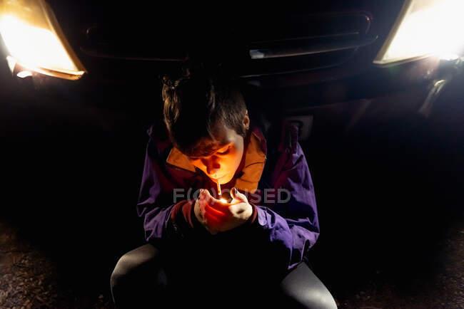 Зверху жінка в фіолетовій і яскравій помаранчевій куртці, яка сидить сама, спираючись на автомобіль з яскравими фарами в темну ніч в Іспанії. — стокове фото