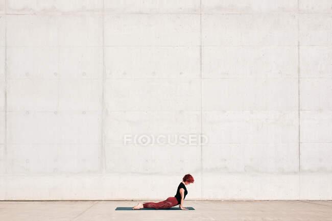 Боковой вид трэнджи подходит спортсменке в костюме бэби-кобры, выполняющей упражнения йоги на спортивном коврике во время тренировки в одиночестве на улице — стоковое фото