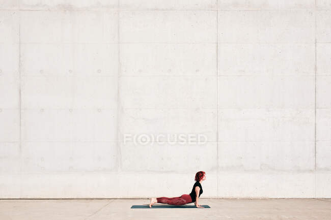 Side view of trendy fit female athlete in sportswear doing baby cobra yoga exercise on sports mat while training alone on street — Stock Photo