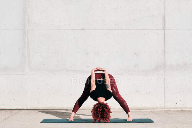 Trendy fit female athlete in sportswear doing wide legged forward bend yoga pose on sports mat while training alone on street — Stock Photo