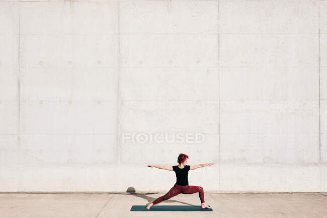 Side view of trendy fit female athlete in sportswear doing warrior two yoga pose on sports mat while training alone on street — Stock Photo