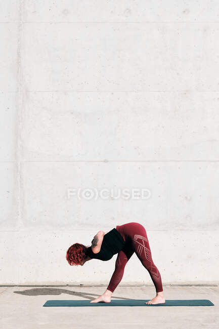 Side view trendy fit female athlete in sportswear doing wide legged forward bend yoga pose on sports mat while training alone — Stock Photo