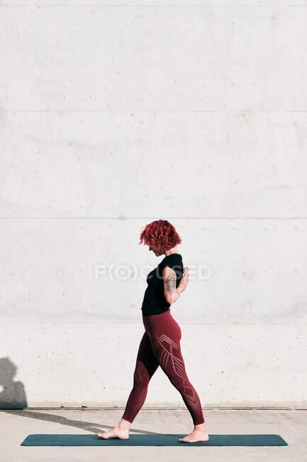 Задумчивая женщина с вьющимися рыжими волосами в спортивной одежде, стоящая на коврике для йоги, протягивая руки к бетонной стене — стоковое фото