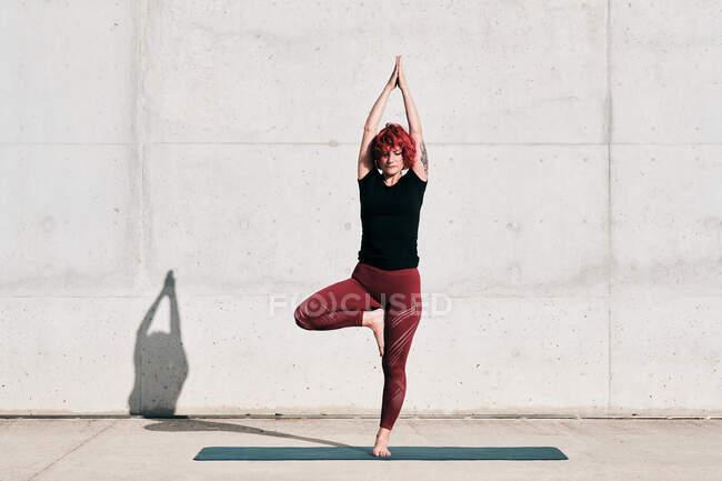 Уверенная босиком спортсменка в спортивной одежде медитирует, стоя в позе врикшасаны с поднятыми руками и намасте — стоковое фото