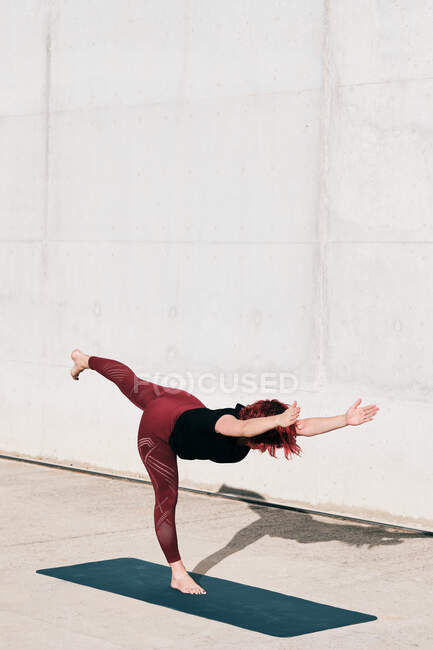 Side view of barefooted woman in sportswear doing yoga in warrior three pose on mat training alone on street against concrete wall in sunlight — Stock Photo