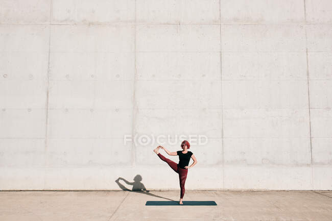 Trendy fit female athlete in sportswear doing extended hand to big toe yoga pose on sports mat while training alone on street — Stock Photo