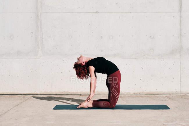 Модная стройная женщина в спортивной одежде, занимающаяся йогой в верблюжьей позе на спортивном коврике одна на улице у бетонной стены в солнечный день — стоковое фото