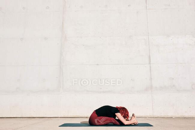 Vista lateral irreconocible flexible descalza atleta femenina con el pelo rizado rojo en ropa deportiva sentado en paschimottanasana — Stock Photo