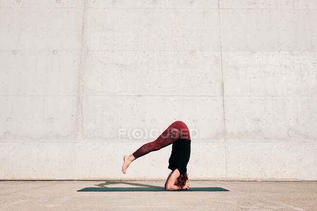 Side view of unrecognizable barefooted female athlete in activewear standing upside down in sirsasana position with legs raised — Stock Photo