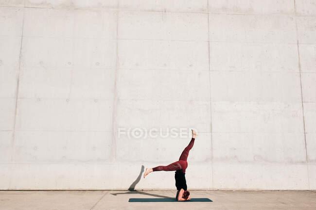 Seitenansicht einer nicht wiederzuerkennenden barfüßigen Athletin in Aktivkleidung, die kopfüber in Sirsasana-Position steht, mit gespaltenen Beinen — Stockfoto