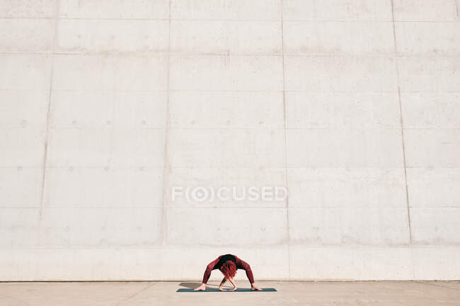 Unrecognizable fit female athlete in sportswear doing wide legged forward bend yoga pose on sports mat while training alone — Stock Photo