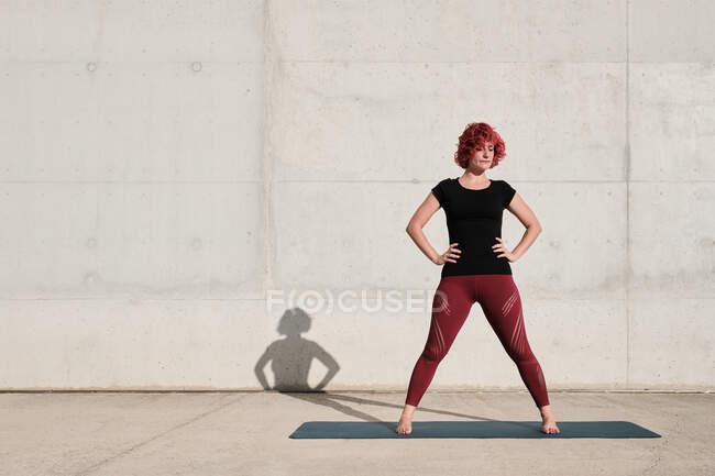Fit durchdachte Frau mit rot gefärbten Locken in Sportbekleidung sinniert, während sie auf Yogamatte gegen Betonwand steht — Stockfoto