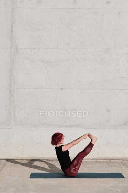 Von oben Seitenansicht einer nicht wiederzuerkennenden barfüßigen Frau mit rotgelockten Haaren in Sportbekleidung, die kopfüber in Bootspose steht — Stockfoto