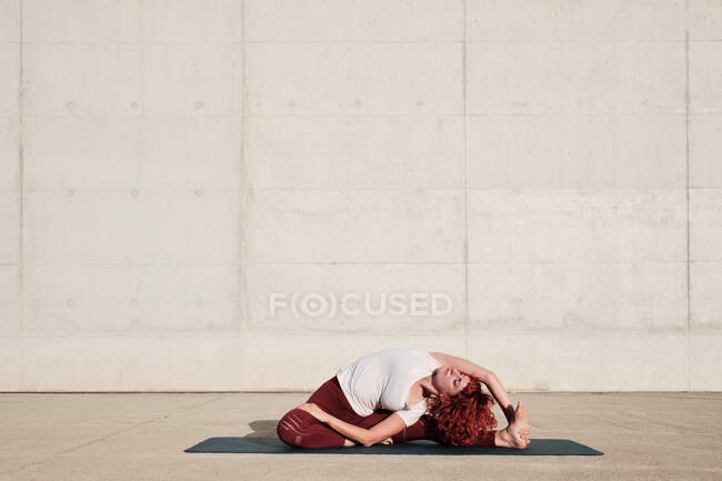 Баронога жінка з заплющеними очима в спортивному одягу робить йогу обернувся головою, щоб коліно позувати на мат тренуючись на самоті на вулиці — стокове фото