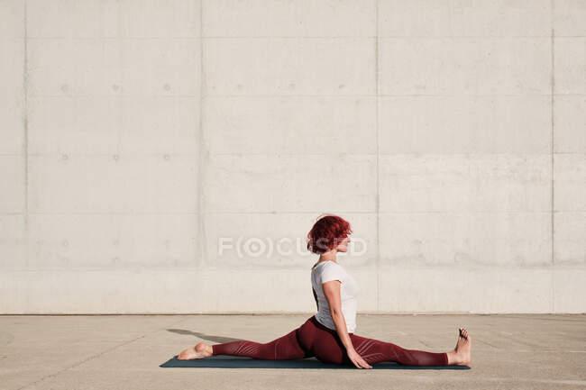 Вид сбоку на обнаженную женщину с закрытыми глазами, занимающуюся йогой в позе обезьяны на коврике на улице — стоковое фото