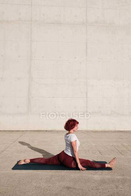 Вид сбоку босой женщины в спортивной одежде, занимающейся йогой в обезьяньей позе на тренировке по коврику в одиночку на улице у бетонной стены — стоковое фото