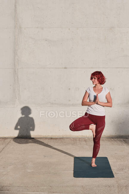 Уверенная босиком спортсменка в спортивной одежде медитирует, стоя в позе врикшасаны с закрытыми к груди руками в намасте — стоковое фото