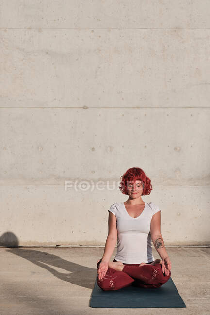 Mujer con pelo rojo y tatuaje en camisa blanca y pantalones borgoña sentada en padmasana con Gyan Mudra y meditando con los ojos cerrados — Stock Photo