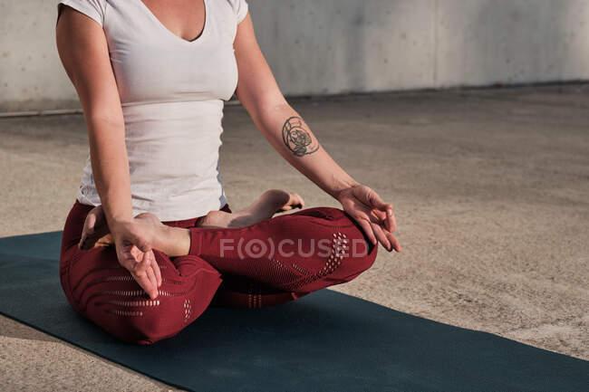 Frau mit Tätowierung in weißem Hemd und weinroter Hose sitzt in Padmasana mit Gyan Mudra und meditiert — Stockfoto