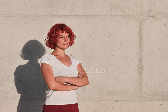 Fit serious woman with curly red dyed hair in sportswear looking away and contemplating while standing with arms crossed against concrete wall — Stock Photo