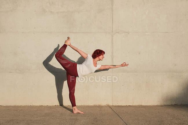 Тренируясь в одиночестве на улице, женщина в спортивном костюме занимается йогой в танцевальной позе — стоковое фото