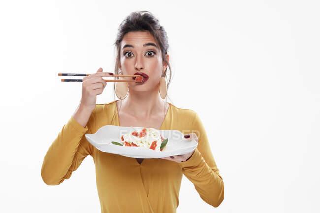 Причудливая молодая женщина с красной помадой, открывающей рот, глядя в камеру, во время еды макарон с соусом с деревянными палочками, изолированными на белом фоне — стоковое фото