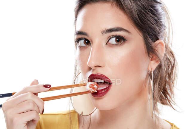 Fantasia giovane donna con rossetto rosso sulla bocca aperta guardando altrove mentre mangia con bacchette di legno isolate su sfondo bianco — Foto stock