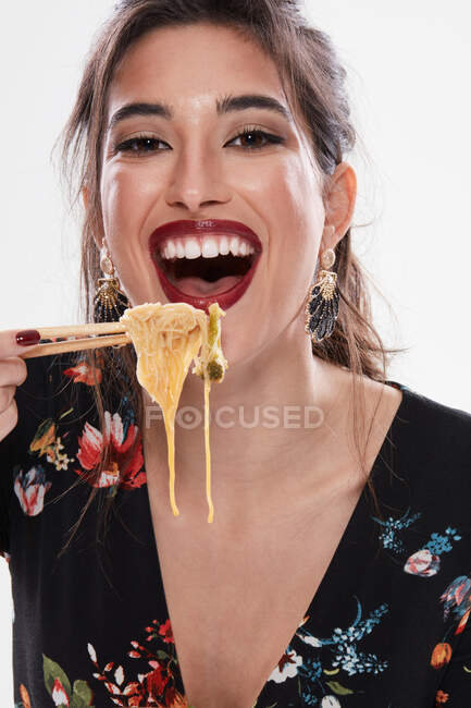 Trendy woman with stylish makeup looking at camera with noodle in mouth and using chopsticks isolated on white background — Stock Photo